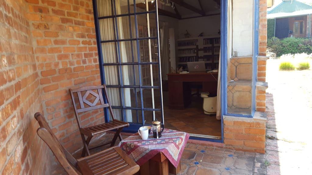 Terrasse meines Backstein-Cottage mit Blick auf Frühstückstisch und Garten im Sonnenlicht