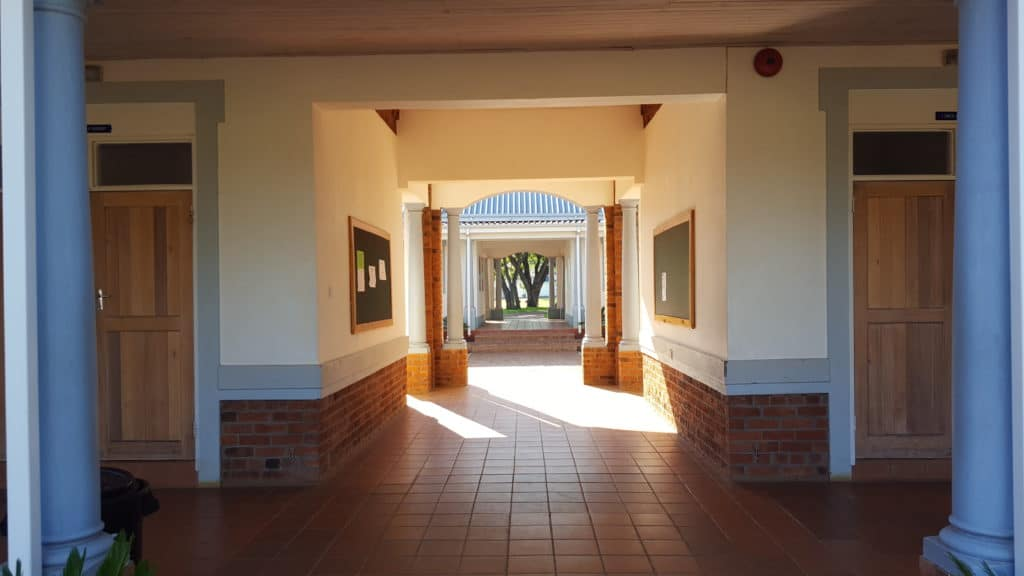 Hellenic Academy: Säulengänge in blau-weiss, terracotta-gefliester Boden, schöne Durchblicke auf Rasen